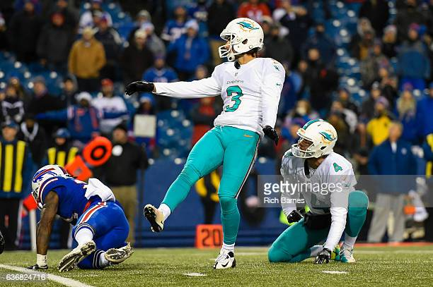 Andrew Franks of the Miami Dolphins watches the game winning field goal after kicking the ball from the hold of with teammate Matt Darr against the...