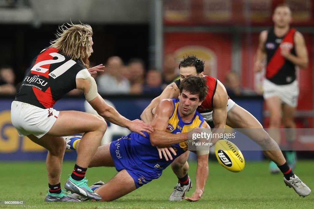 Andrew Gaff of the Eagles gets his handball away while being tackled during the round 14 AFL match between the West Coast Eagles and the Essendon Bombers at Optus Stadium on June 21, 2018 in Perth, Australia.