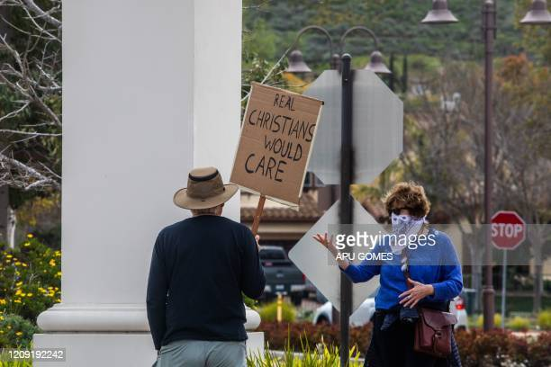 Andrew Goethe and Kathryn Seawant protest outside the Godspeaker Calvary Chapel sanctuary, where Pastor Rob McCoy leaded a communion ceremony after...