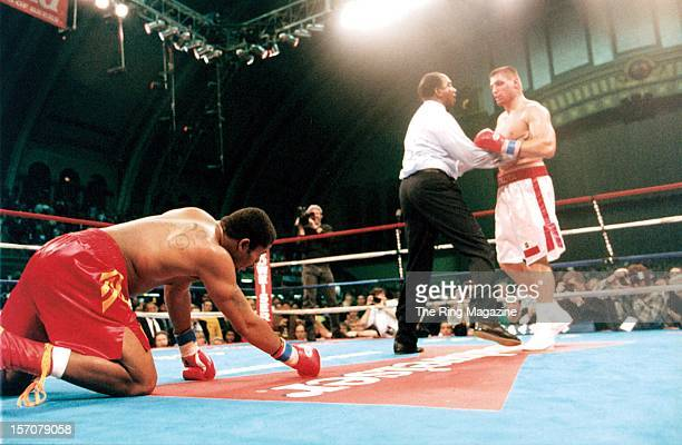 Andrew Golota is pulled away after knocking down Riddick Bowe during a fight at the Convention Center on December 14 1996 in Atlantic City New Jersey...