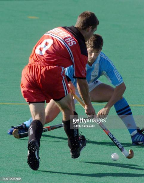 Andrew Griffiths of Canada moves the ball as Carlos Retegui of Argentina tries to defend during the Men's Field Hockey gold medal match at the Pan Am...