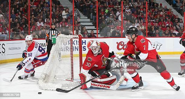 Andrew Hammond of the Ottawa Senators follows the puck as team mate Kyle Turris reaches for it and Evgeny Kuznetsov of the Washington Capitals skates...