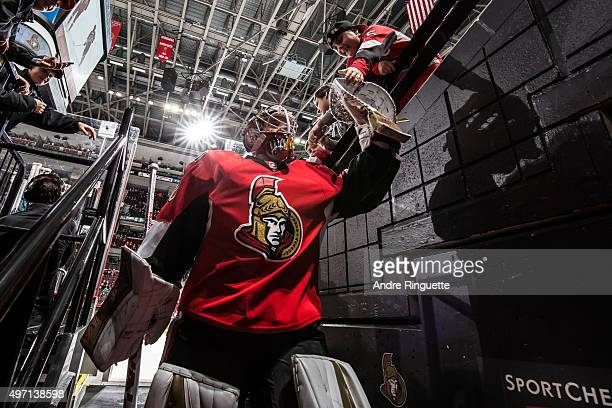 Andrew Hammond of the Ottawa Senators highfives a young fan after warmup prior to a game against the New York Rangers at Canadian Tire Centre on...