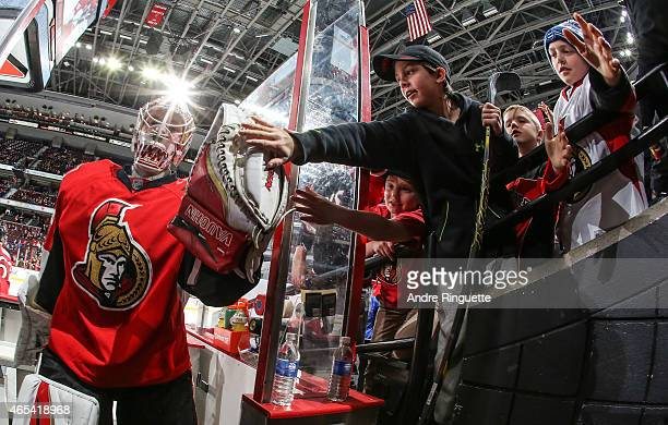 Andrew Hammond of the Ottawa Senators highfives young fans as he leaves the ice after warmup prior to a game against the Buffalo Sabres at Canadian...
