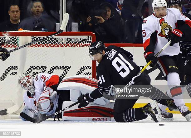 Andrew Hammond of the Ottawa Senators is injured during the first period as he makes the save on John Tavares of the New York Islanders at the...
