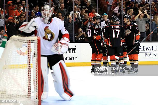 Andrew Hammond of the Ottawa Senators looks on as Corey Perry Ryan Kesler and Ryan Getzlaf of the Anaheim Ducks celebrate a goal during the third...
