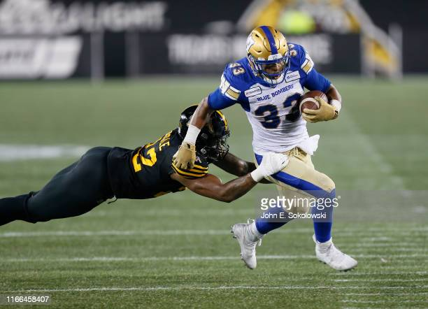 Andrew Harris of the Winnipeg Blue Bombers breaks a tackle by Justin Tuggle of the Hamilton TigerCats at Tim Hortons Field on July 26 2019 in...