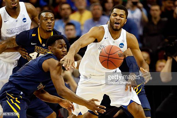 Andrew Harrison of the Kentucky Wildcats battles for the ball with Juwan Staten and Jevon Carter of the West Virginia Mountaineers in the first half...