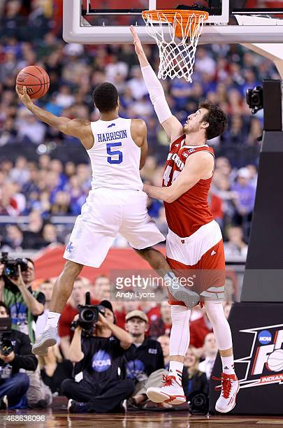 Andrew Harrison of the Kentucky Wildcats drives to the basket against Frank Kaminsky of the Wisconsin Badgers in the first half during the NCAA Men's...
