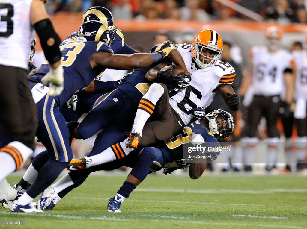 Andrew Hawkins #16 of the Cleveland Browns is dragged down by Lamarcus Joyner #20 and E.J. Gaines #33 of the St. Louis Rams during the second quarter at FirstEnergy Stadium on August 23, 2014 in Cleveland, Ohio.