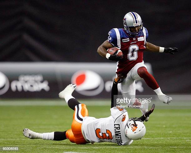 Andrew Hawkins of the Montreal Alouettes jumps over Tad Crawford of the BC Lions while rushing the ball during the Eastern Finals at Olympic Stadium...