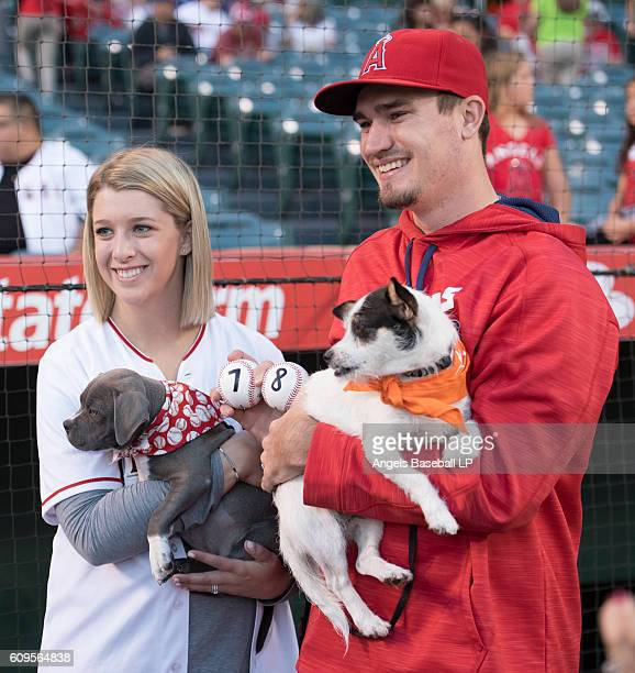 Andrew Heaney of the Los Angeles Angels of Anaheim and his wife Jordan Heaney left pose holding dogs on the field as part of a fundraiser run by...