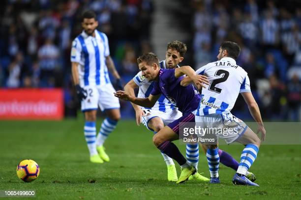 Andrew Hjulsager of Celta Vigo is challanged by Joseba Zaldua of Real Sociedad and Adnan Januzaj of Real Sociedad during the La Liga match between...