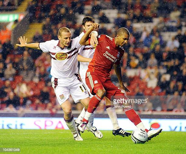 Andrew Holt of Northampton Town tussles with david Ngog of Liverpool during the Carling Cup 3rd round game between Liverpool and Northampton Town at...