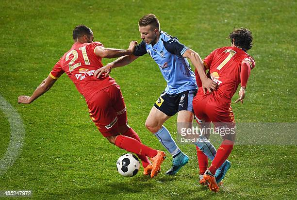 Andrew Hoole of Sydney competes for the ball against Tarek Elrich of United and Pablo Snchez Alberto of United during the FFA Cup Round of 16 match...