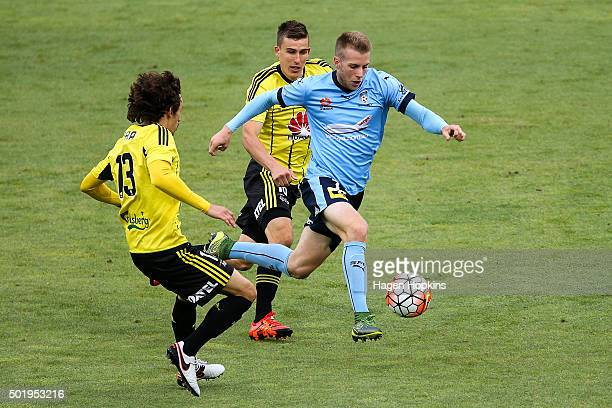 Andrew Hoole of Sydney FC breaks through the defence of Albert Riera and Louis Fenton of the Phoenix during the round 11 ALeague match between the...