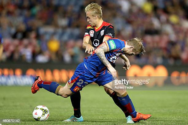 Andrew Hoole of the Jets contests the ball against Jamas Jeggo of Adelaide United during the round 12 A-League match between the Newcastle Jets and...