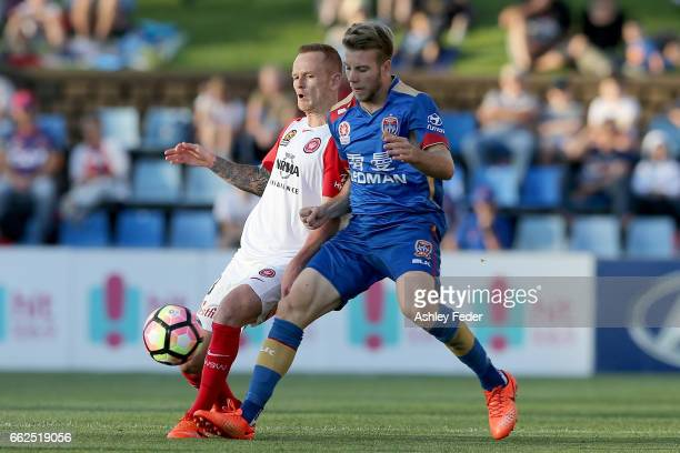 Andrew Hoole of the Jets is tackled by Jack Clisby of the Wanderers during the round 25 ALeague match between the Newcastle Jets and the Western...