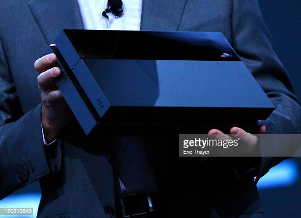 Andrew House President and Group CEO Sony Computer Entertainment Inc holds up a Playstation 4 at the Sony Playstation E3 2013 press conference June...