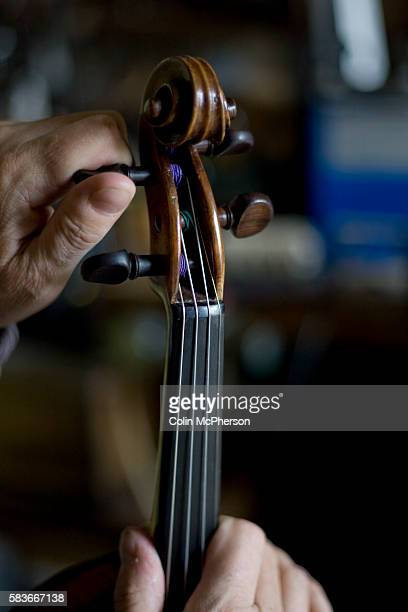 Andrew Hutchinson testing the strings on a violin under repair at his workshop at Hoylake Wirral north west England Mr Hutchinson trained at Newark...