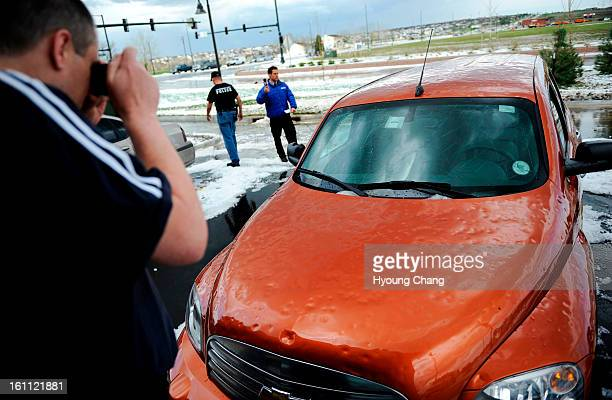 Andrew Jackson is taking picture of his car damaged by hail near the corner of 104th and Chambers in commerce city on Wednesday Hyoung Chang/ The...