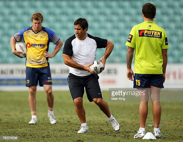 Andrew Johns demonstrates a move as Brett Finch and Tim Smith of the Eels look on during a Parramatta Eels training session at Parramatta Stadium on...
