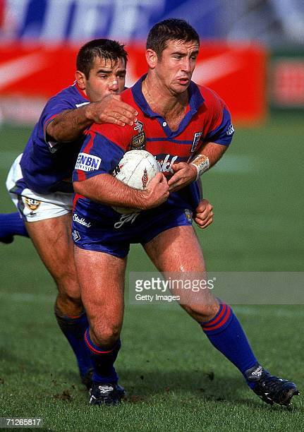 Andrew Johns of the Knights is tackled by Stacey Jones of the Warriors during a ARL match between the Newcastle Knights and the Auckland Warriors at...
