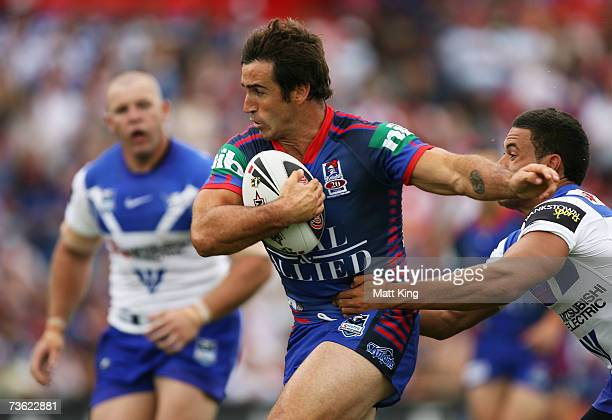 Andrew Johns of the Knights takes on the Bulldogs defence during the round one NRL match between the Newcastle Knights and the Bulldogs at...