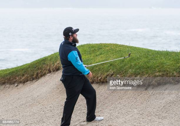 Andrew Johnston checks his ball position from the sand trap on the 18th green at the conclusion of first round play of the ATT Pebble Beach ProAm in...