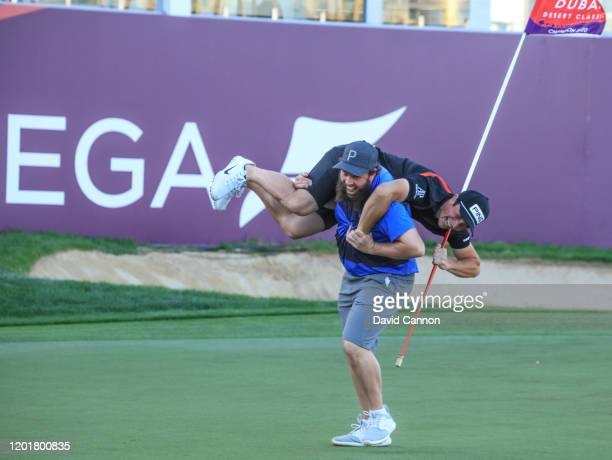 Andrew Johnston of England lifts Viktor Hovland up after he had holed his final putt with a two iron to tie with a score of six on the 18th hole...