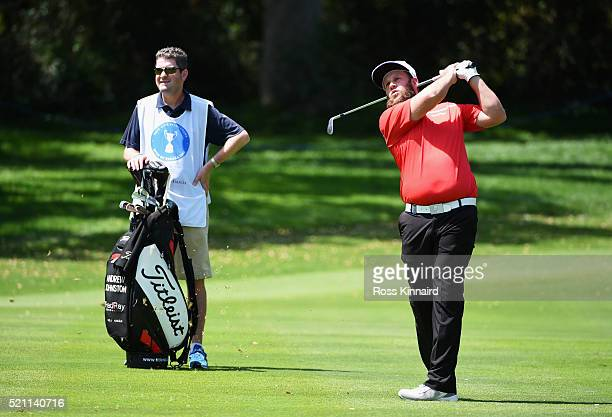 Andrew Johnston of England plays his second shot on the 18th hole as his caddie looks on during day one of the Open de Espana at Real Club Valderrama...