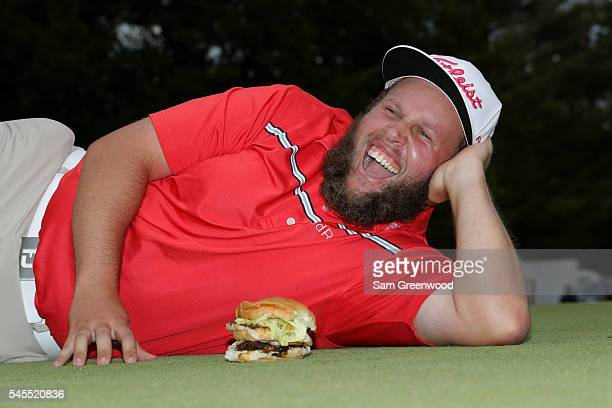 Andrew Johnston of England poses for a portrait with a hamburger after the third round of the World Golf Championships Bridgestone Invitational at...