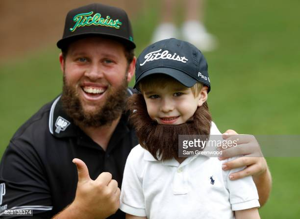 Andrew Johnston of England poses with a young fan during a practice round prior to the 2017 PGA Championship at Quail Hollow Club on August 9 2017 in...