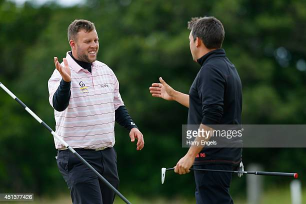 Andrew Johnston of England shakes hands with compatriot Jason Barnes after finishing on the eighteenth on day three of the 2014 Scottish Hydro...