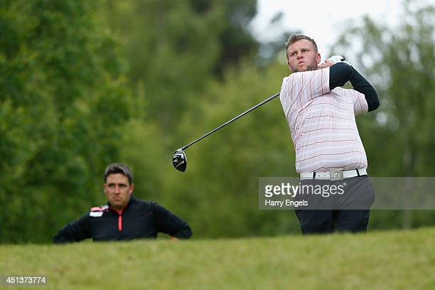 Andrew Johnston of England tees off at the seventeeth watched by compatriot Jason Barnes on day three of the 2014 Scottish Hydro Challenge hosted by...