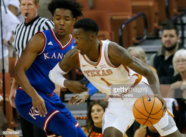Andrew Jones of the Texas Longhorns drives around Devonte' Graham of the Kansas Jayhawks at the Frank Erwin Center on December 29 2017 in Austin Texas