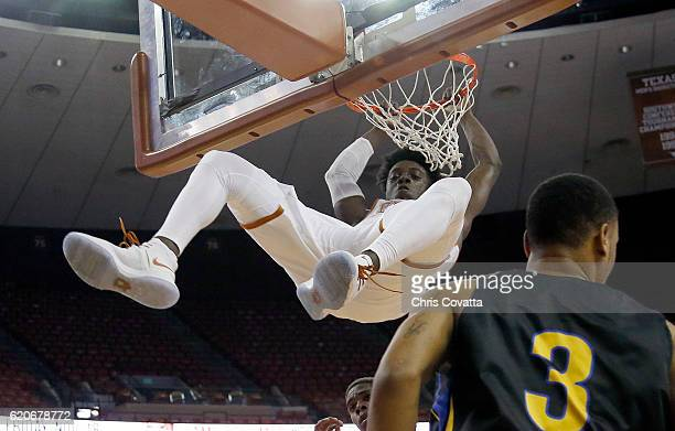 Andrew Jones of the Texas Longhorns hangs on the rim after slam dunking against the Angelo State Rams during an exhibition game at the Frank Erwin...