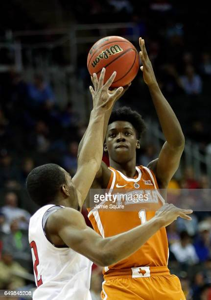 Andrew Jones of the Texas Longhorns shoots over Keenan Evans of the Texas Tech Red Raiders during the first round of the Big 12 Basketball Tournament...