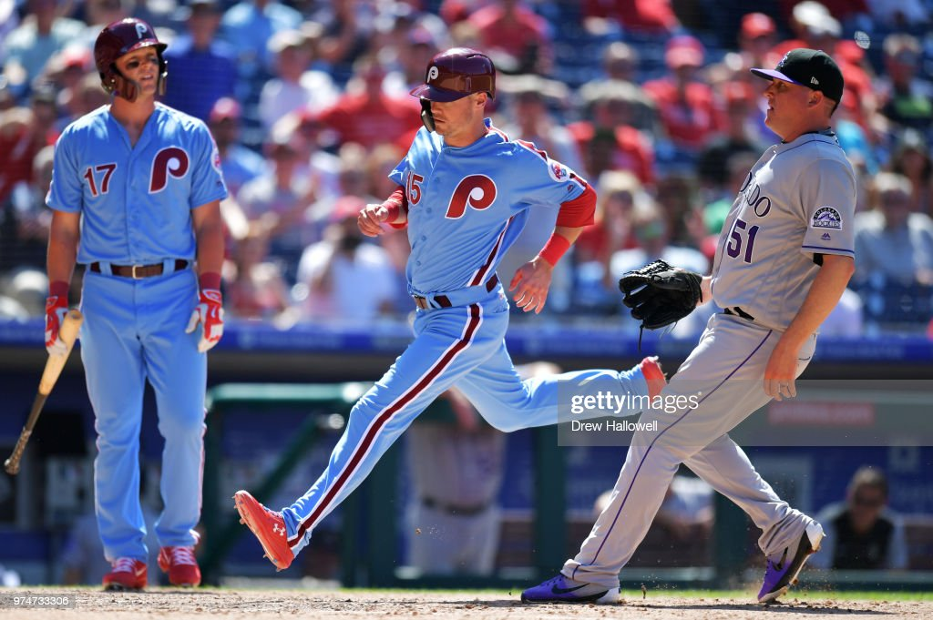 Andrew Knapp #15 of the Philadelphia Phillies runs by Jake McGee #51 of the Colorado Rockies to score on a passed ball as Rhys Hoskins #17 looks on in the seventh inning at Citizens Bank Park on June 14, 2018 in Philadelphia, Pennsylvania.