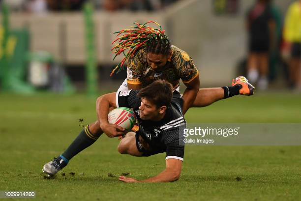 Andrew Knewstubb of New Zealand is tackled by Justin Geduld of the South Africa during day 1 of the HSBC Cape Town Sevens Pool A match 24 between New...