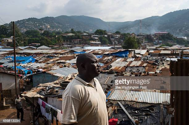 Andrew Kondoh prepares to pick up the body of a 7month old baby in Race Course area of Freetown Sierra Leone on Sunday November 23 2014