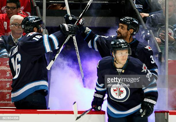 Andrew Ladd and Dustin Byfuglien of the Winnipeg Jets tap sticks as they get set to face the Detroit Red Wings at the MTS Centre on December 29 2015...