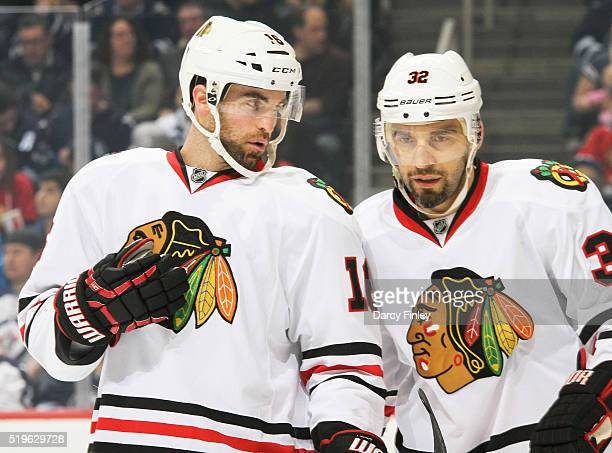 Andrew Ladd and Michal Rozsival of the Chicago Blackhawks discuss strategy during a first period stoppage in play against the Winnipeg Jets at the...
