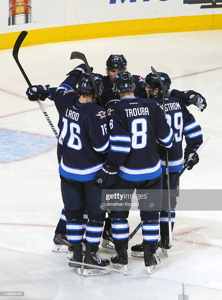 Andrew Ladd #16, Bryan Little #18, Blake Wheeler #26, Jacob Trouba #8 and Tobias Enstrom #39 of the Winnipeg Jets celebrate a third period goal against the Colorado Avalanche at the MTS Centre on March 19, 2014 in Winnipeg, Manitoba, Canada.