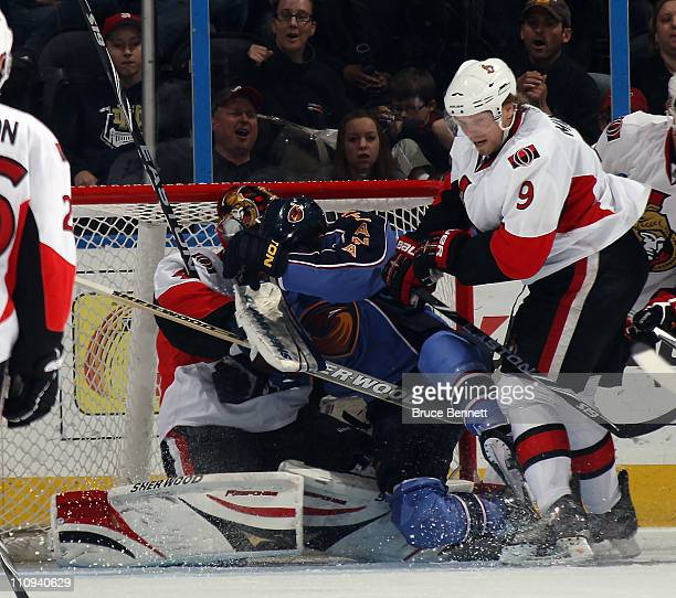 Andrew Ladd of the Atlanta Thrashers lands on top of Craig Anderson of the Ottawa Senators at the Philips Arena on March 27 2011 in Atlanta Georgia...