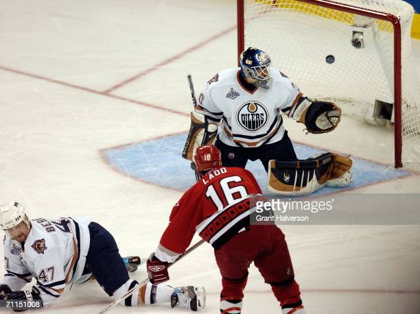 Andrew Ladd of the Carolina Hurricanes scores the first goal over goaltender Jussi Markkanen and MarcAndre Bergeron of the Edmonton Oiler during the...