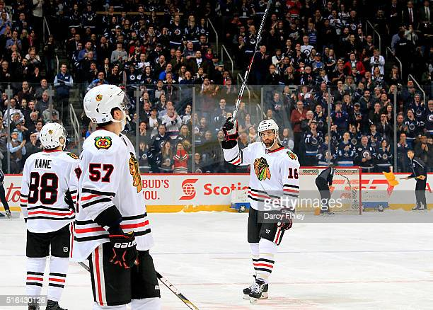 Andrew Ladd of the Chicago Blackhawks acknowledges the standing ovation given by the fans as teammates Patrick Kane and Trevor van Riemsdyk watch the...