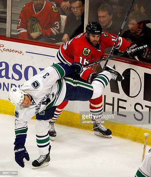 Andrew Ladd of the Chicago Blackhawks and Kevin Bieksa of the Vancouver Canucks get tangled up along the boards in Game Two of the Western Conference...