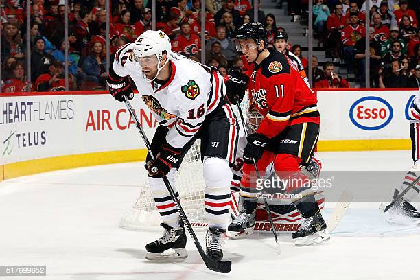 Andrew Ladd of the Chicago Blackhawks skates against Mikael Backlund of the Calgary Flames during an NHL game at Scotiabank Saddledome on March 26...