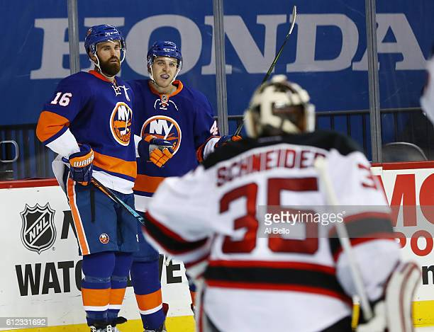 Andrew Ladd of the New York Islanders celebrates his second period goal with Colin Markison against Cory Schneider of the New Jersey Devils during...